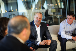 Photo of men in business suits smiling during a meeting